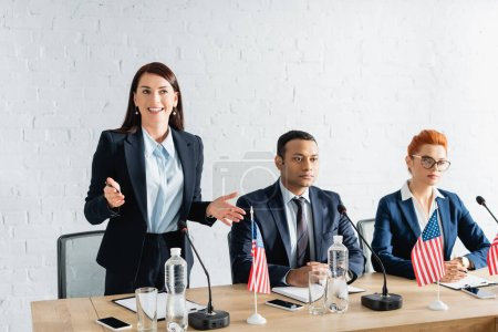 Smiling female politician with open arms talking, while standing near interracial colleagues in boardroom