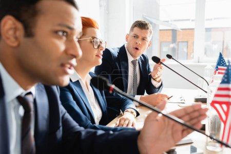 Foto de Político irritado con la boca abierta mirando a su colega hablando en micrófono, mientras se sienta a la mesa en la sala de juntas en un primer plano borroso - Imagen libre de derechos