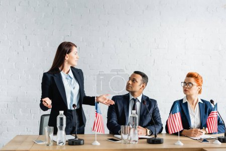 Female politician with open arms looking at interracial colleagues sitting in boardroom