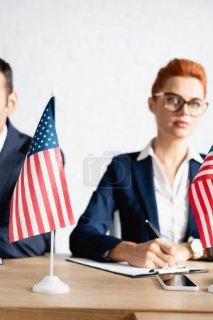 Photo pour Petits drapeaux américains sur la table avec des gens flous sur le fond - image libre de droit