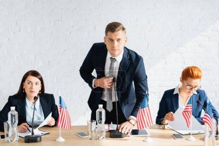 Photo pour Homme en tenue formelle regardant la caméra, tout en se penchant et en touchant le microphone dans la salle de réunion - image libre de droit