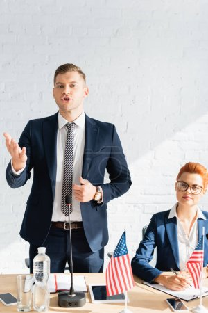 Confident politician gesturing, while talking, standing near smiling colleague during political party congress in boardroom