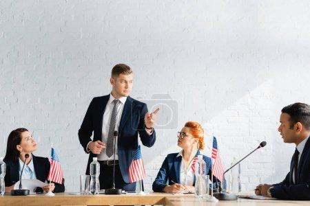 Photo pour Homme politique sérieux pointant du doigt tout en se tenant debout et regardant collègue lors du congrès du parti politique dans la salle de conférence - image libre de droit