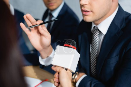 partial view of journalist with microphone interviewing politician during party congress on blurred foreground