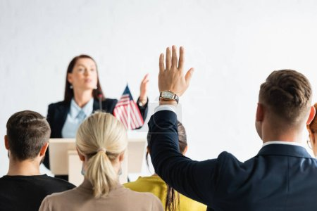 agitador político apuntando con la mano al hombre con la mano levantada sobre fondo borroso