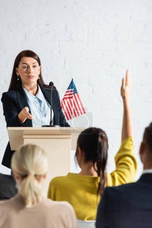 Photo pour Haut-parleur pointant la main vers la femme avec la main levée dans la salle de conférence, au premier plan flou - image libre de droit