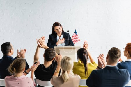 Photo pour Candidat reconnaissant tenant la main sur la poitrine tout en se tenant devant les applaudissements des électeurs dans la salle de conférence - image libre de droit