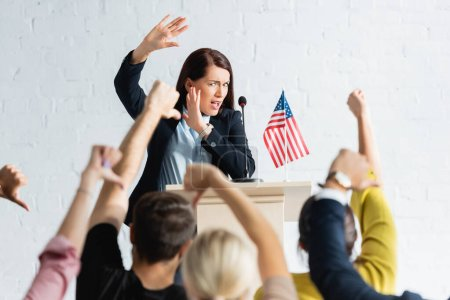 shocked speaker standing in front of voters showing thumbs down in conference hall