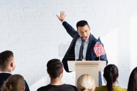 Photo pour Agitateur indien excité geste tout en parlant aux électeurs dans la salle de conférence, flou au premier plan - image libre de droit