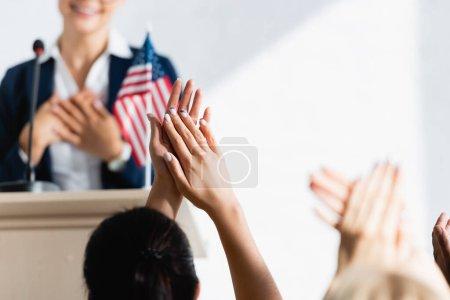 Photo pour Agitateur politique reconnaissant tenant la main sur la poitrine devant les électeurs iapplaudissant n salle de conférence, flou au premier plan - image libre de droit