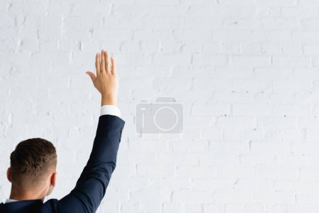 back view of man voting with raised hand against white brick wall
