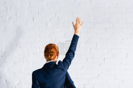 back view of woman voting with raised hand against white brick wall