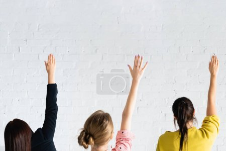back view of women voting with raised hands against white brick wall