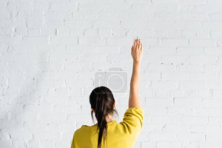 back view of woman voting with hand in air against white brick wall
