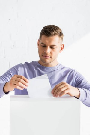 Photo pour Homme insérant le bulletin de vote dans l'isoloir - image libre de droit