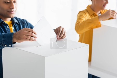 indian man inserting ballot into polling box near woman on blurred background