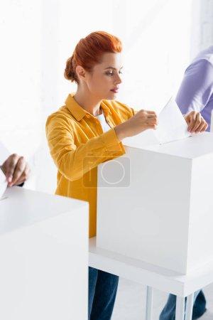 Photo pour Femme insérant le bulletin dans la boîte de scrutin près des électeurs sur fond flou - image libre de droit