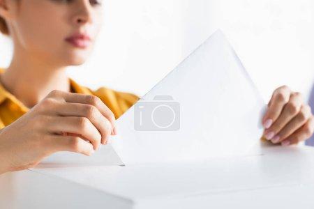 Photo pour Vue partielle de la femme insérant son bulletin de vote dans une urne sur fond flou - image libre de droit