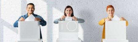 Photo for Multicultural electors inserting ballots into polling booths, banner - Royalty Free Image