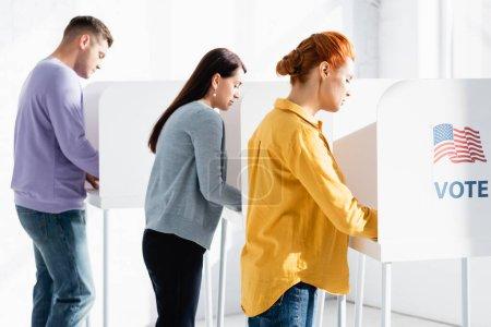 Photo pour Électeurs dans les bureaux de vote avec drapeau américain et lettrage du vote sur fond flou - image libre de droit