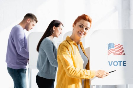 smiling woman pointing with pen on american flag and vote inscription on polling booth on blurred background