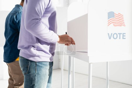 Photo for Cropped view of multicultural men in polling booth with american flag and vote inscription - Royalty Free Image