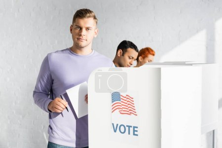 Photo for Man looking at camera while holding ballot near polling booth with american flag and vote lettering on blurred background - Royalty Free Image