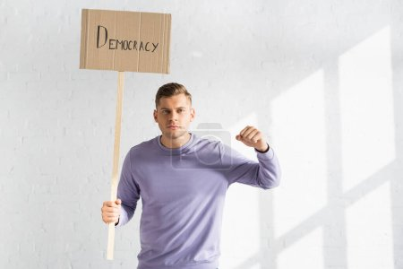 strict man with clenched fist holding placard with democracy inscription against white brick wall