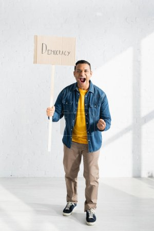 aggressive indian man screaming while holding placard with democracy lettering against white brick wall