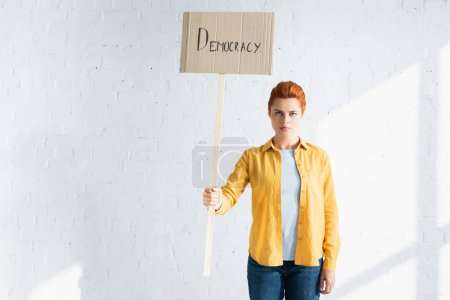 serious woman holding placard with democracy lettering against white brick wall