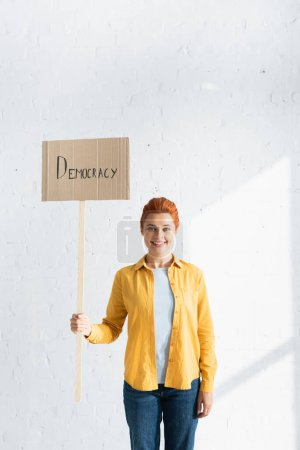 smiling woman holding placard with democracy lettering against white brick wall