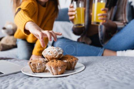 abgeschnittene Ansicht eines Kindes, das Muffin von einem Teller in der Nähe einer Mutter nimmt, die Orangensaft auf verschwommenem Hintergrund hält