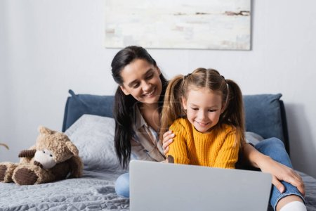 cheerful woman looking at daughter using laptop in bedroom
