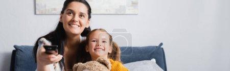 Photo pour Joyeuses mère et fille regarder la télévision ensemble à la maison, bannière - image libre de droit