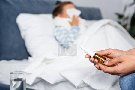 mujer sosteniendo aerosol nasal cerca de hija enferma acostada en la cama sobre fondo borroso
