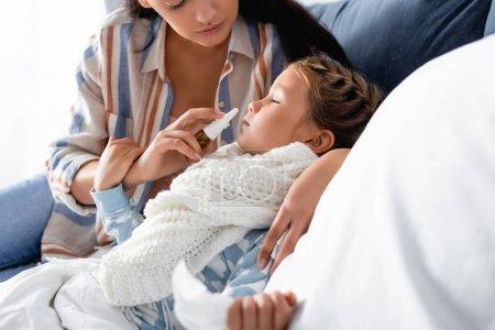 mujer usando aerosol nasal a hija enferma que sufre de secreción nasal en primer plano borroso