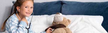 Photo pour Fille gaie regardant caméra tout en examinant ours en peluche avec stéthoscope, bannière - image libre de droit