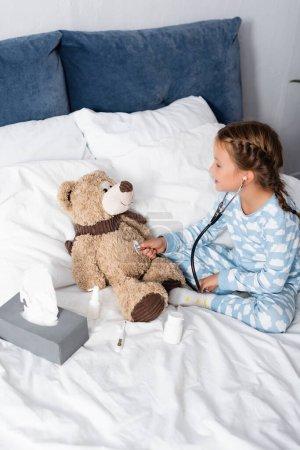 chica examinando osito de peluche con estetoscopio mientras juega en la cama