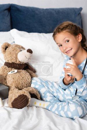 sonriente niño sosteniendo pastillas botella mientras con osito de peluche en el dormitorio