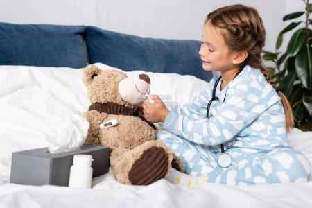 niño curando oso de peluche con aerosol nasal mientras juega en la cama