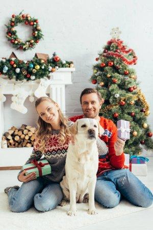 Photo pour Joyeux couple tenant des cadeaux et assis près du chien et l'arbre de Noël à la maison - image libre de droit