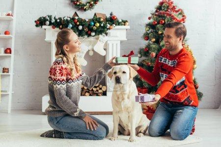 Photo pour Un couple souriant échangeant des cadeaux assis près du chien et de l'arbre de Noël à la maison - image libre de droit
