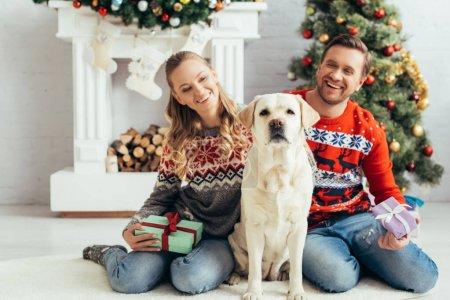 Photo pour Heureux couple tenant des cadeaux et assis près du chien et arbre de Noël - image libre de droit