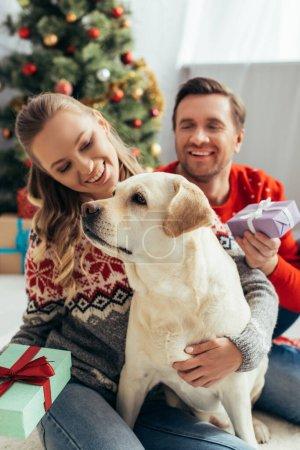 Photo pour Couple tenant des cadeaux près de chien et arbre de Noël à la maison - image libre de droit