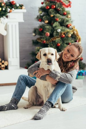 smiling woman in sweater sitting on floor and cuddling labrador near christmas tree