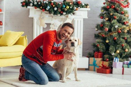 Photo pour Excité homme en pull câlin labrador près décoré arbre de Noël - image libre de droit