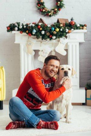 Photo pour Homme heureux en pull câlin labrador dans appartement décoré, concept de Noël - image libre de droit