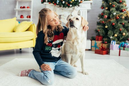 happy girl in warm sweater sitting near labrador in decorated living room, christmas concept