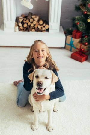 happy girl in warm sweater cuddling labrador in decorated living room, christmas concept