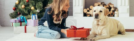 Photo for Joyful kid in sweater sitting near labrador and holding christmas present in decorated living room, banner - Royalty Free Image